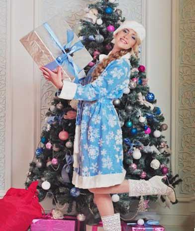 Снегурочка с подарком возле елки.